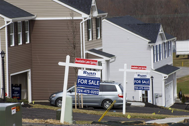 Model homes and for sale signs line the streets in Zelienople, Pa., on March 18, 2020.
