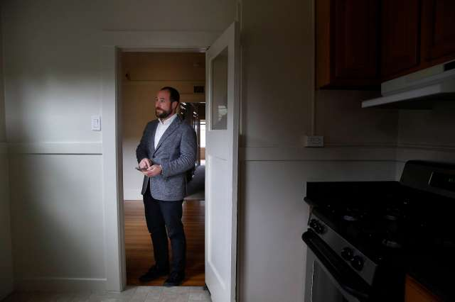 J.J. Panzer, president and broker Real Management Company, stands in the doorway to the kitchen in a vacant unit in an apartment building managed by Real Management Company in April.